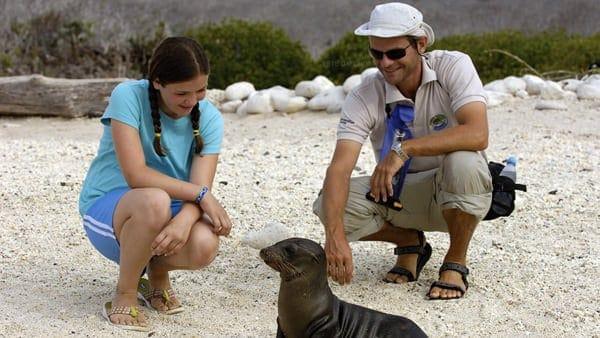 Galapagos traveler and small ship naturalist guide sitting looking at a sea lion pup.