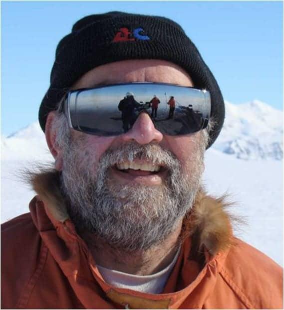 Crew member of small ship cruise smiling in Antarctica.