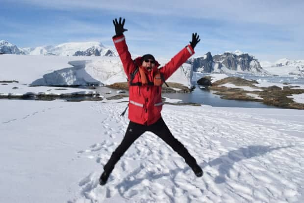 Excited guest from small cruise ship Jumping on the snow in Antarctica with arms up in air.