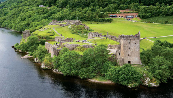 Aerial view of Urquhart Castle set along Scotland's Great Glen waterway, surrounded by bright green trees and grass.