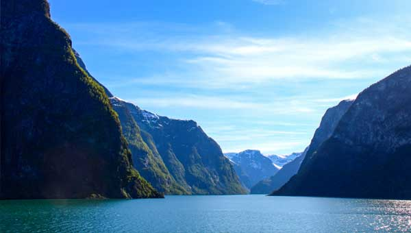 Norwegian fjord with green cliffs and blue sky and small clouds above seen on a Northern Europe tour.