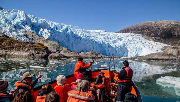 Travelers in a small orange boat approach a blue-white glacier on a Patagonia cruise.