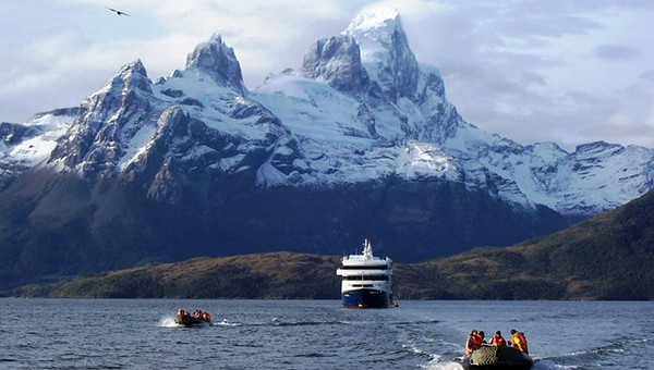 Patagonia Australis cruise ship with mountains in the background and two skiffs heading toward the camera.