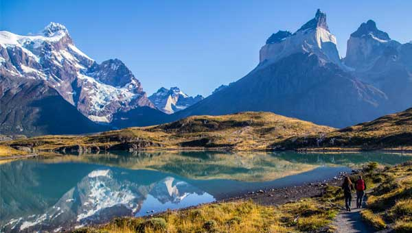 Iconic Patagonia tours scene with hikers on a path and a glacial lake with mountains in front of them.