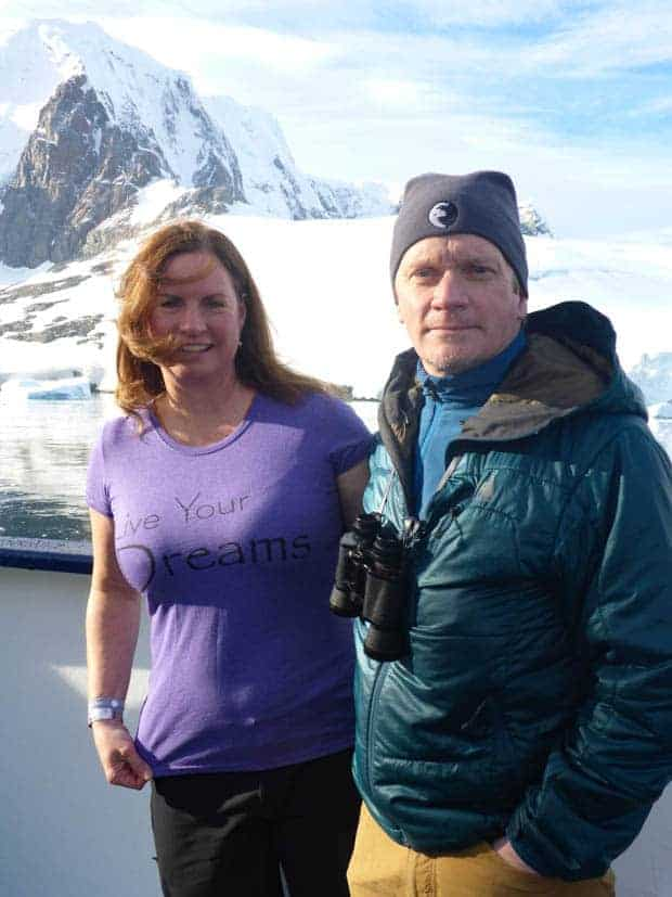 Two guests aboard a small ship expedition cruise in Antarctica with binocular and mountains in the background.