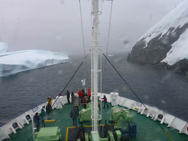 Bow of a small ship cruise going through a narrow channel in Antarctica.