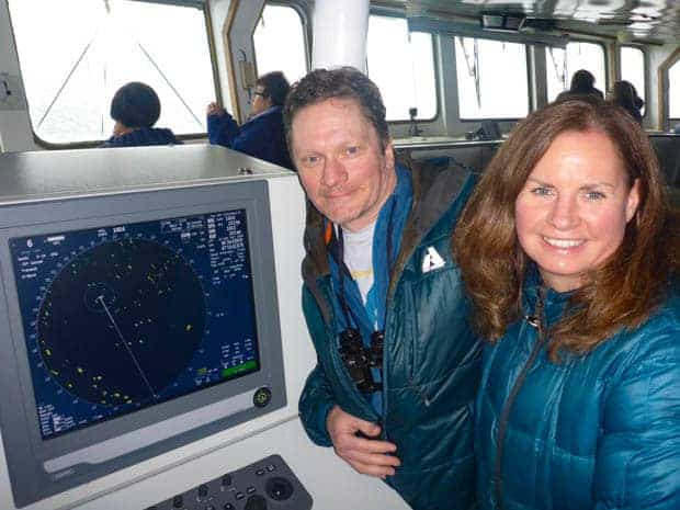 Two guests smiling by the navigation map on the bridge of  a small ship cruise in Antarctica.