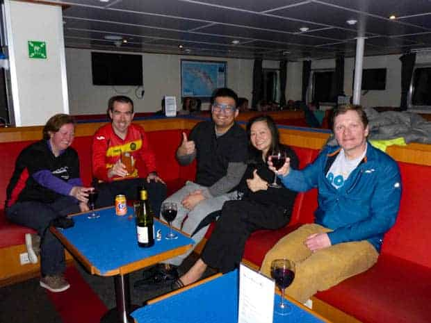 Guests aboard a small ship cruise in Antarctica drinking wine together and giving a thumbs up.