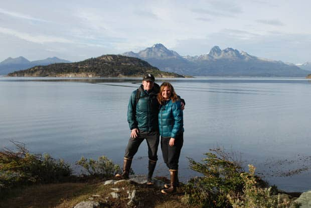Two people smiling in Tierra del Fuego National Park with mountains in the background.