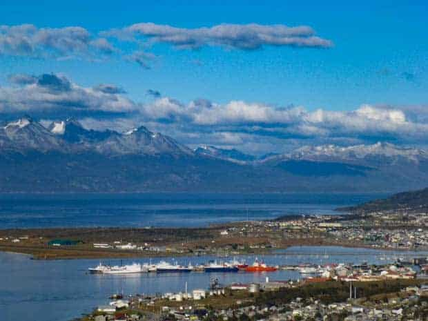 Ushuaia seen from a view point with the harbor and mountains in the background.
