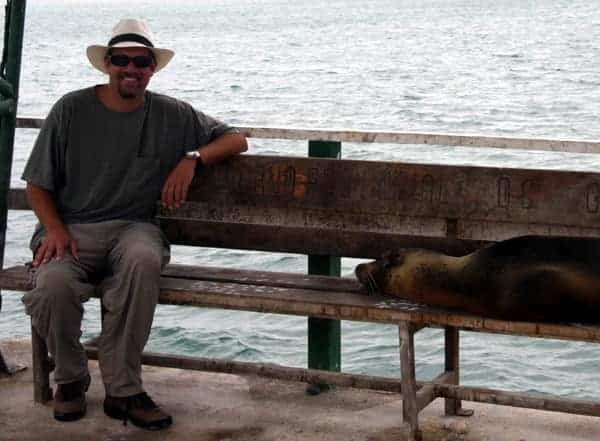 Galapagos traveler sitting on a bench with a sleeping sea lion.