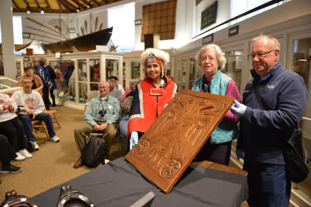 Sheldon Jackson Museum with small ship travelers observing a Tlingit carved wood door.