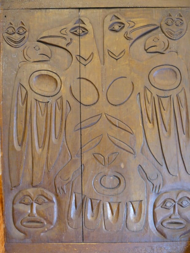 Tlingit carved wood door of 2 ravens and fish with other face carvings.