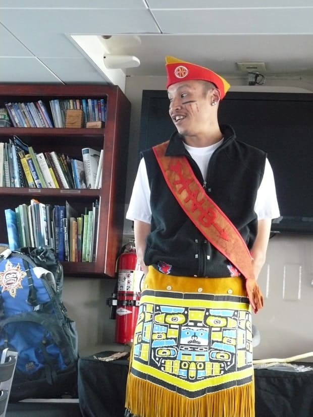 Native cultural Tlinget guide giving a presentation with some traditional dress.
