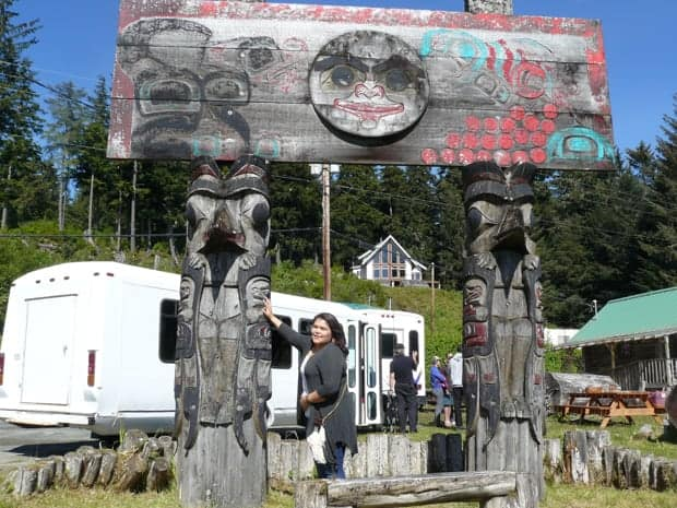 Tlingit town of Kake with 2 totems and a large mantel on top with Alaskan travelers milling about from white buses.