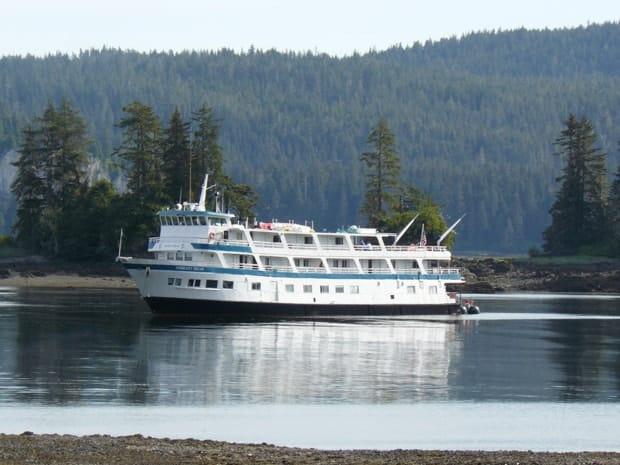 Small ship cruise anchored in Alaskan waters off a low tide Alaskan coast.