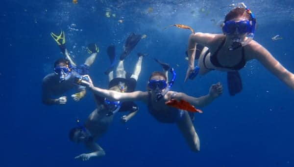 Group of 5 snorkelers in deep blue water with dark blue masks & snorkels & black fins during a Belize family vacation.