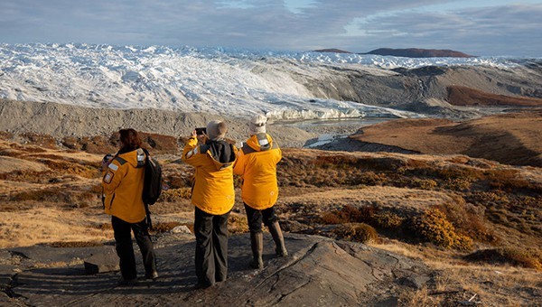 Three cruise passengers in yellow jackets standing on brown soil take photos of a large white glacier in Canada.