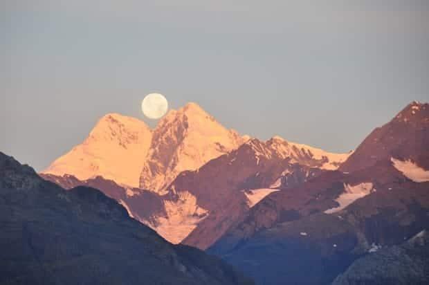 Full moon sitting atop the peak of a mountain range at dusk.