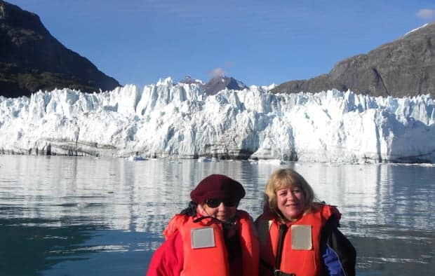 2 small ship travelers in front of Grand Pacific glacier in Glacier Bay National Park.