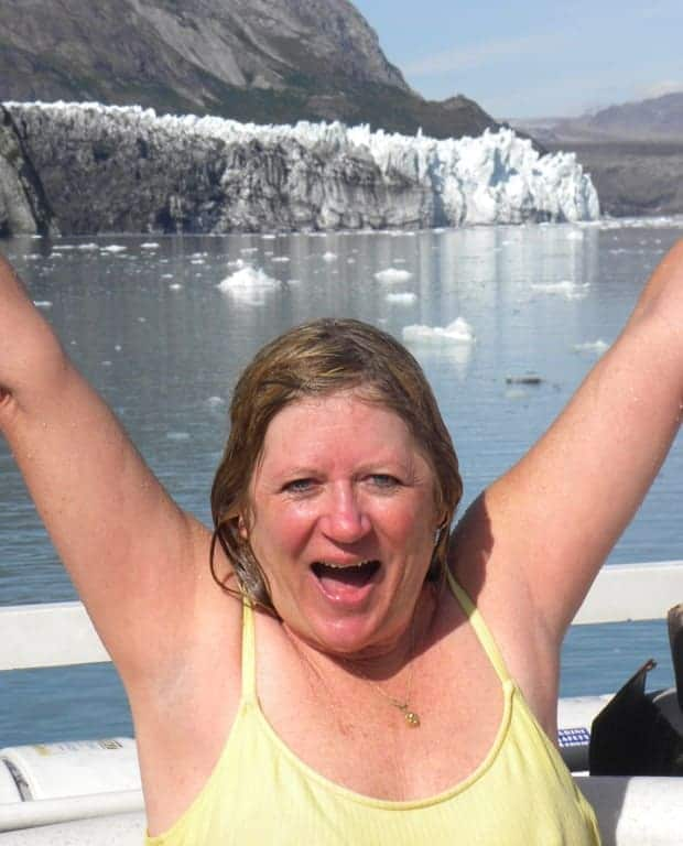 Happy small ship traveler excited after jumping in the cold waters of Alaska with a tidewater glacier in the background.