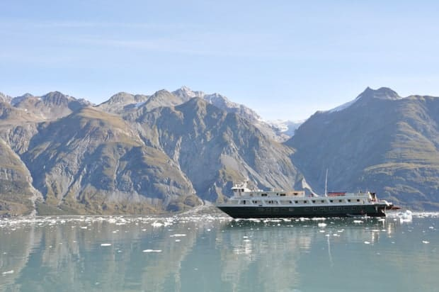 Small ship cruise boat sailing in Alaska surrounded by small ice chunks and mountain range.
