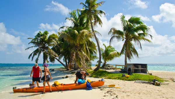 3 kayakers unload an orange kayak on a sandy beach under palm trees & blue sky during a Belize cruise excursion.