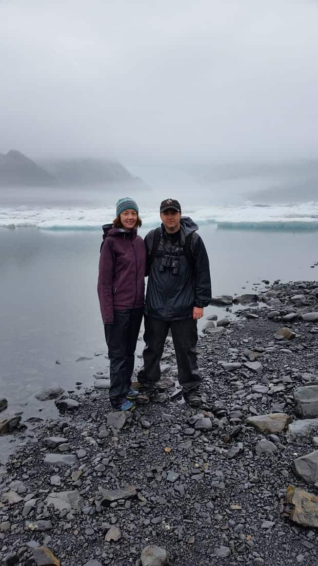 Rocky shoreline with small icebergs on a misty day with 2 travelers in Alaska.