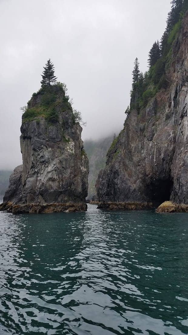 Kenai Fjords granite rock tower and cliff with a cave from the ocean.