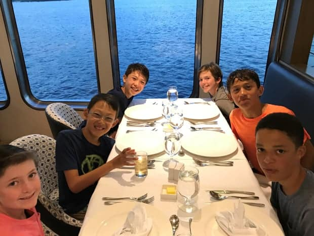 Children with their own table next to the window in the dining room aboard their small ship Galapagos cruise.