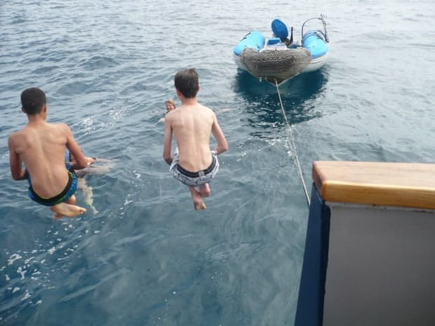 Children jumping off their small ship cruise into the blue water of the Galapagos.