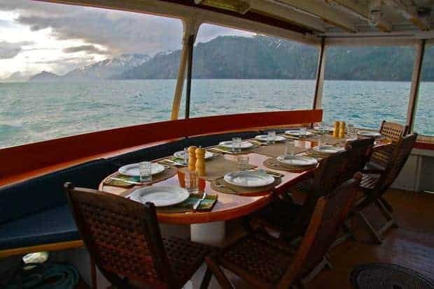 Dinner table aboard the small ship Sea Wolf surrounded by windows looking at the mountains of Alaska.