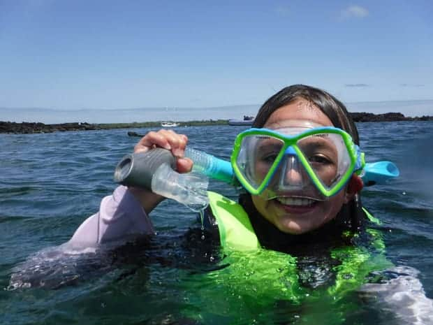 Child smiling with snorkel and mask on in the water on a small ship cruise snorkel tour.