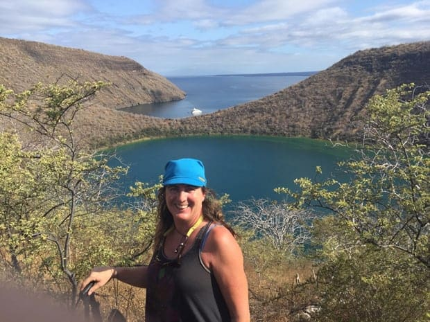 Happy guest from a small ship cruise  at a viewpoint on a hiking tour in the Galapagos.