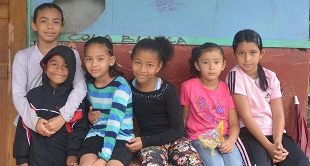 Local school children smiling in front of the Laguna de Tortuguero School in Costa Rica.
