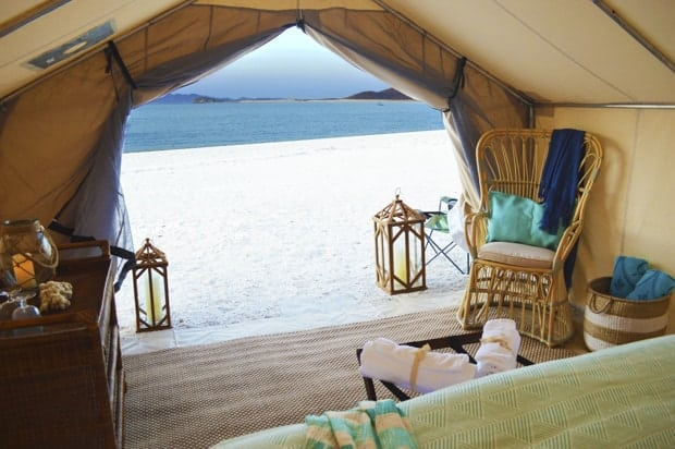 A inside view of a glamping tent with bed, chairs, dresser set on a white sandy beach next to the ocean.
