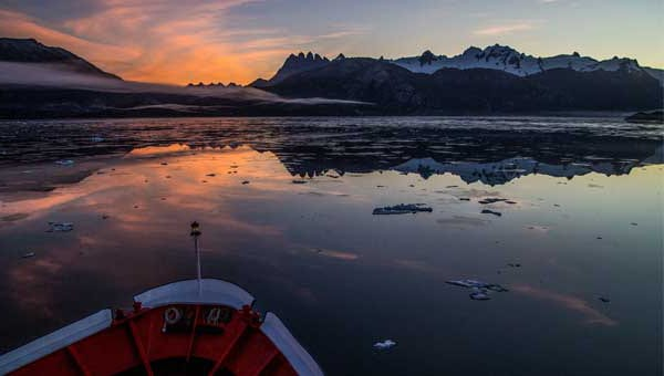 Bow of small expedition ship facing snow-capped peaks at sunset during a Chilean fjords cruise.
