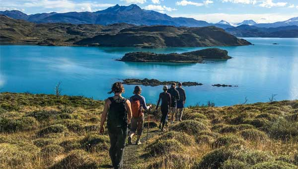 A line of hikers follow the trail through a grassy meadow down to a glacial lake with jagged peaks in the background, commonly seen on Chile Patagonia tours.