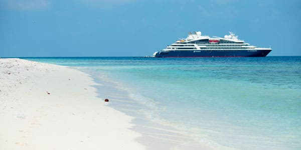 Luxury Caribbean cruise ship with blue & white exterior sits offshore of a private island white-sand beach.