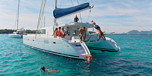 Group of family travelers jump off the back of a private catamaran into calm turquoise waters during a Caribbean family vacation.