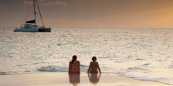 2 women sit at water's edge on a sandy beach at sunset with their private Caribbean catamaran charter yacht in the distance.