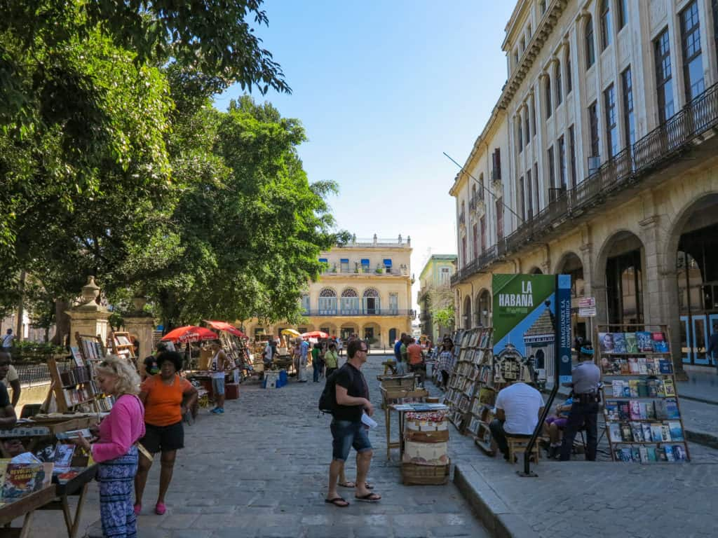 A traveler walking alone through a street market in Cuba