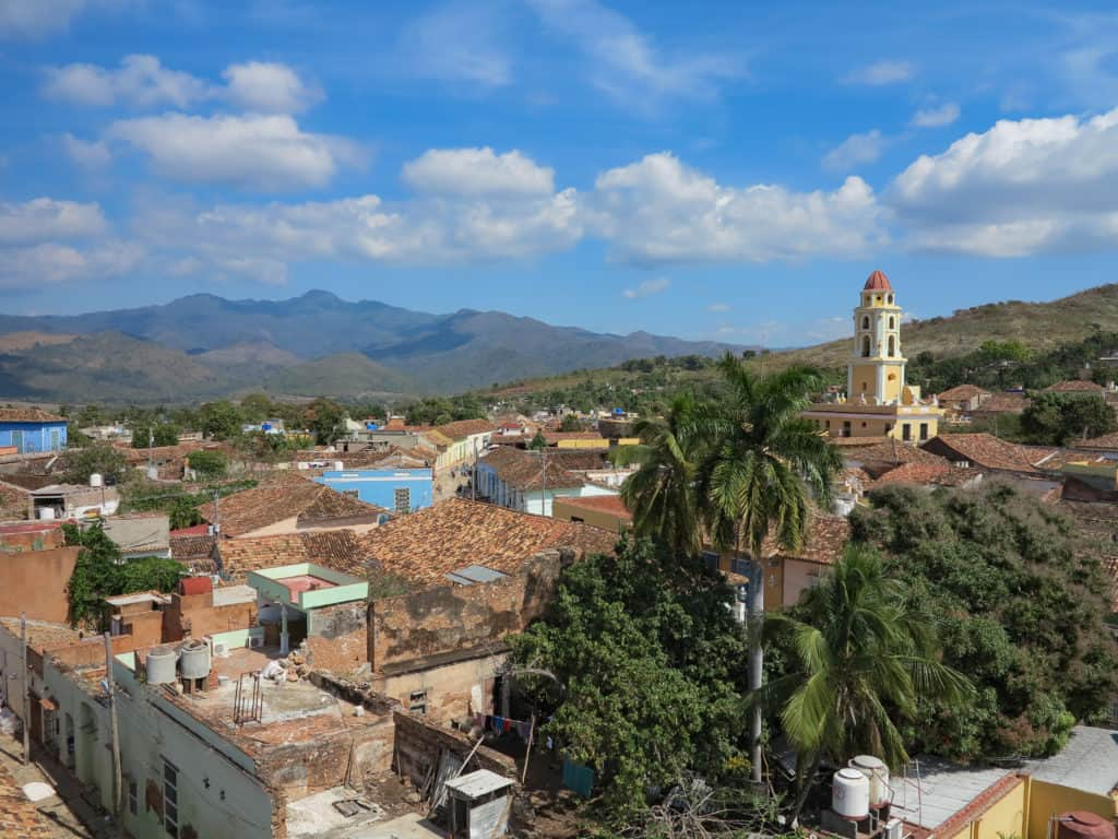 An overview of a Cuban city with a large yellow and white church rising above the red roofs