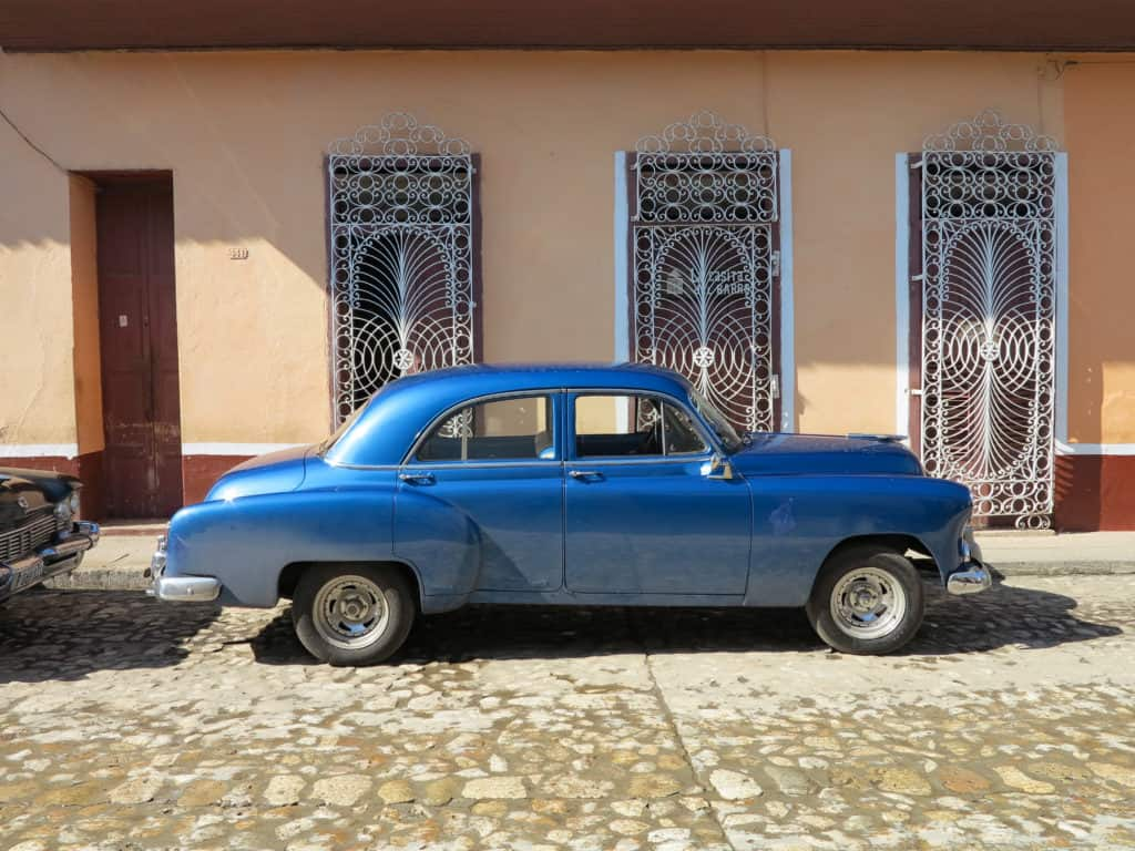 Old classic blue car in front of ornate white window covers and orange building