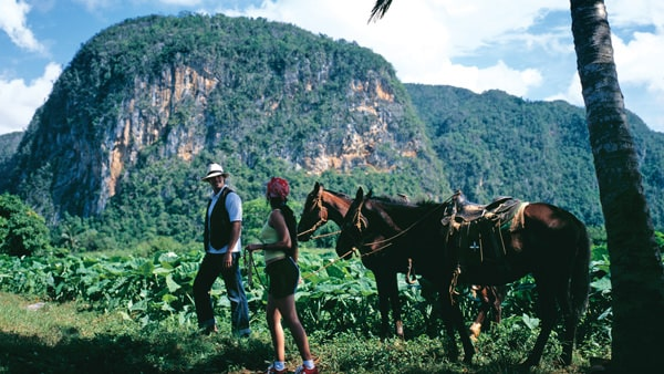 people walking with horses on a Cuban land tour