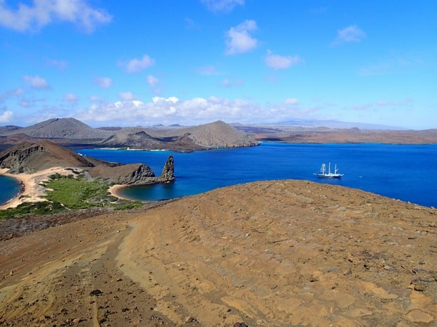 View of Pinnacle rock from a hike in the Galapagos with a small ship cruise in the distance.