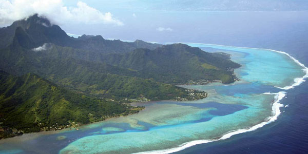 Aerial view of jagged green volcanic peaks leading down to turquoise waters seen during luxury South Pacific cruises.