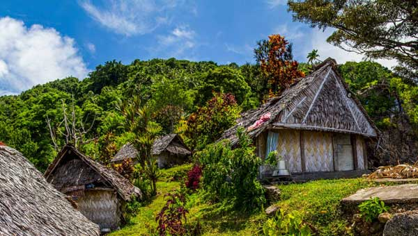 Thatch-roof huts line a lush green hillside on a sunny day during a South Pacific vacation.