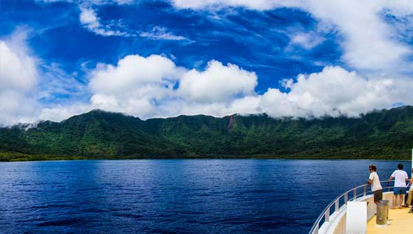 Man stands on bow of small ship looking at deep blue sea & verdant green hillside on a partly cloudy but bright day during a small ship cruise in the Pacific Islands.