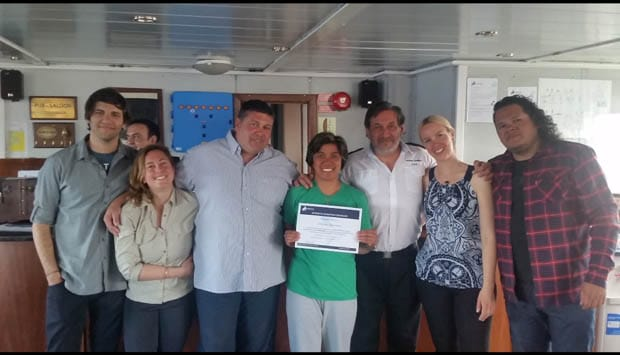 Guests aboard a small ship cruise in Antarctica pose with their Antarctica Expedition Certificates and crew members on the bridge.